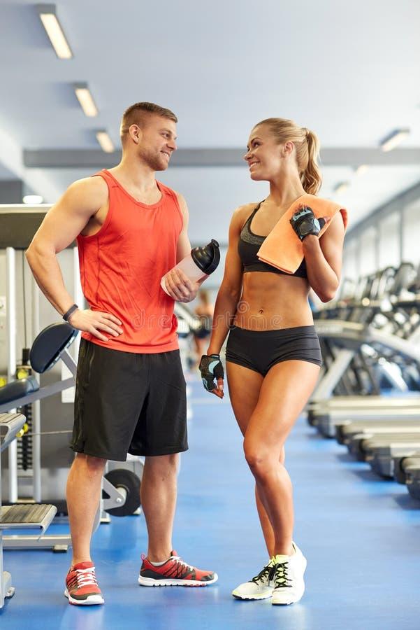 微笑的男人和妇女谈话在健身房 免版税库存照片