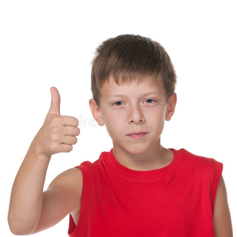 微笑的男孩举行他的赞许 库存照片