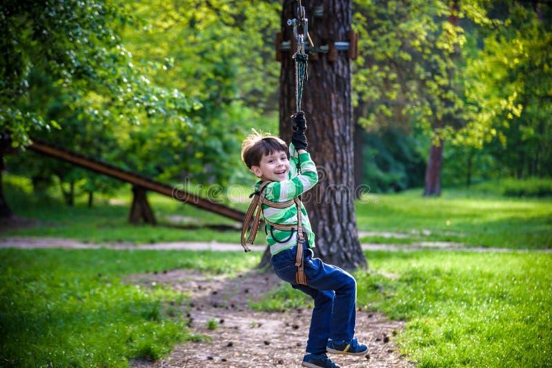 微笑的男孩乘坐邮编线 邮编线的愉快的孩子 孩子通过绳索障碍桩 库存图片