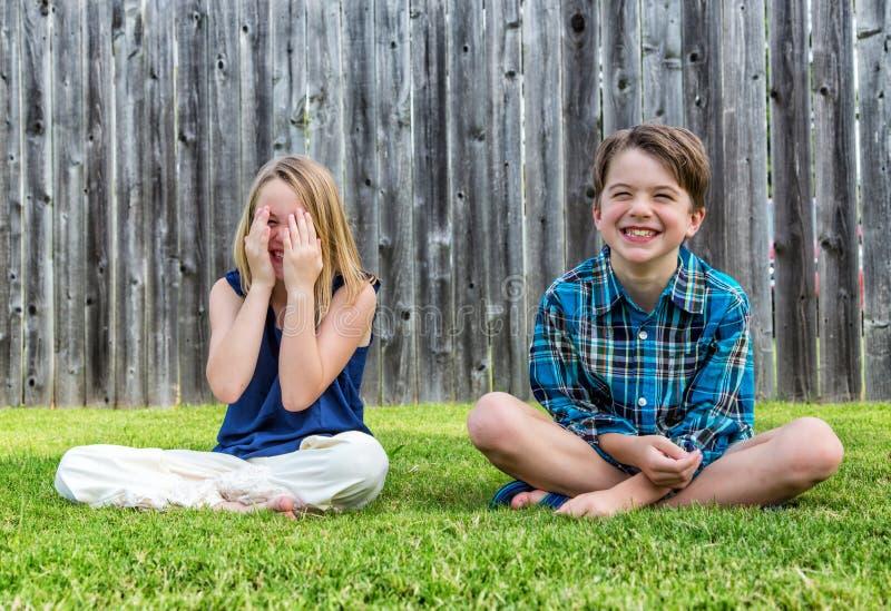 微笑的男孩和女孩草的 库存照片