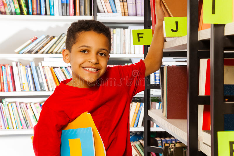 微笑的男孩在书架上把手放并且拿着书 库存图片