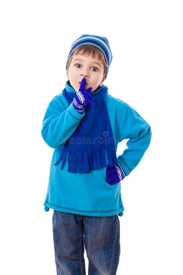 微笑的男孩在冬天给显示沈默标志穿衣 免版税图库摄影