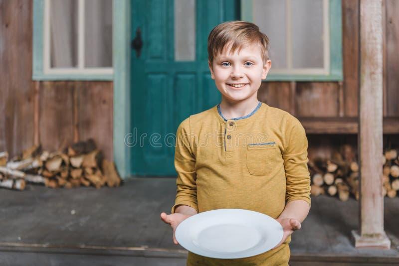 微笑的男孩在手上的拿着空的板材 免版税库存照片