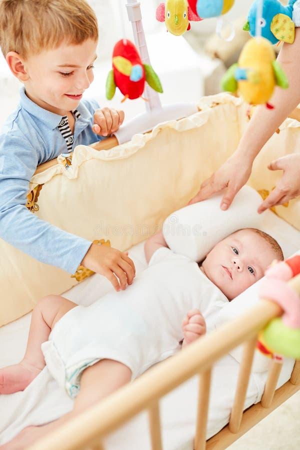 微笑的男孩在新出生的婴孩看 库存照片