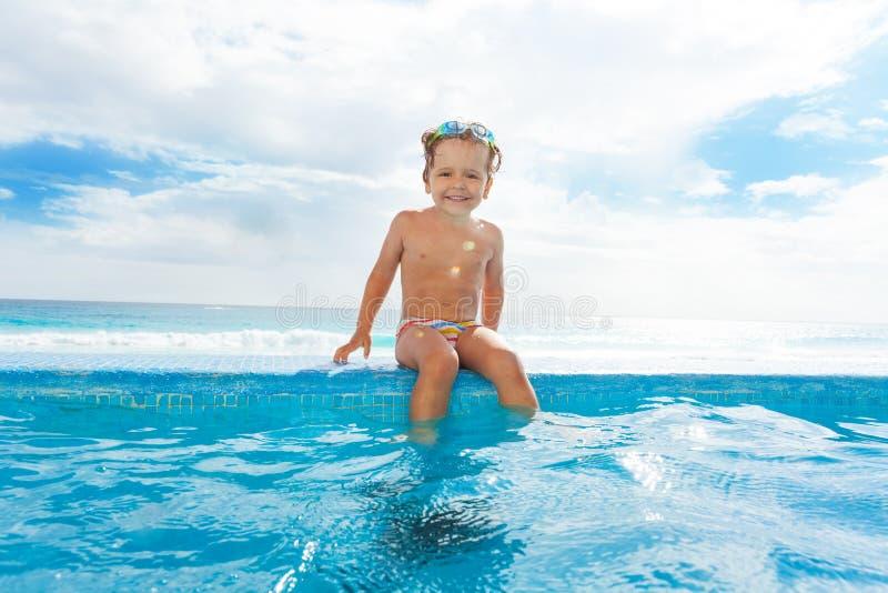 微笑的男孩坐扔石头的房客在水附近 免版税图库摄影