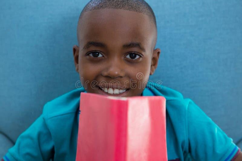微笑的男孩特写镜头画象有红色小说的在家 免版税库存图片