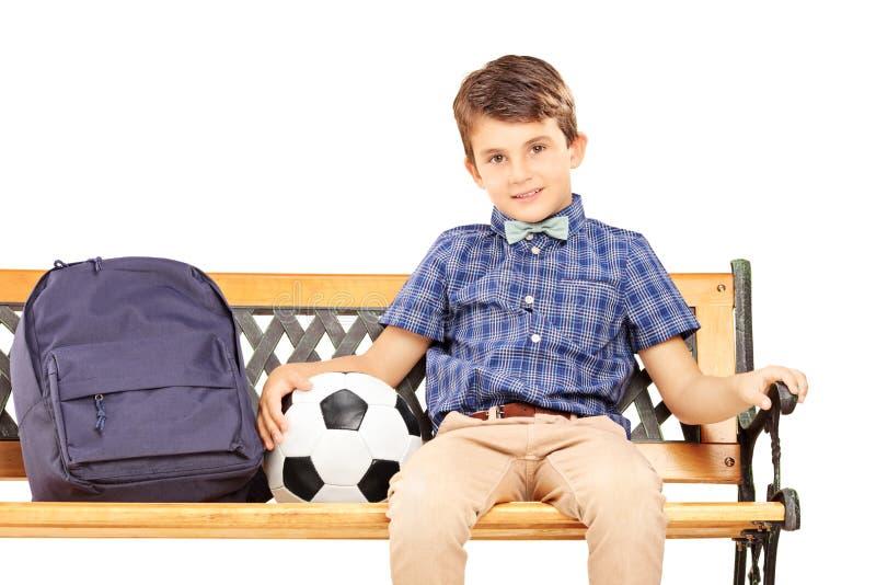 微笑的男小学生坐与书包和球的一条长凳 免版税库存照片