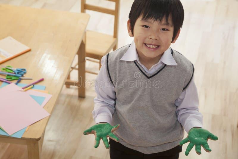 微笑的男小学生手指画法画象在艺术课,北京的 免版税库存图片