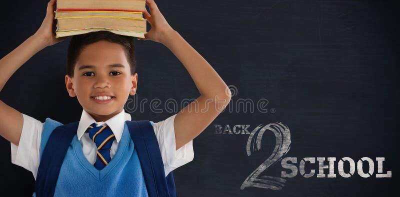 微笑的男小学生运载的书的综合图象在头的在白色背景 免版税库存照片