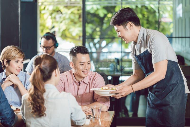 微笑的男性侍者服务的食物在餐馆 图库摄影