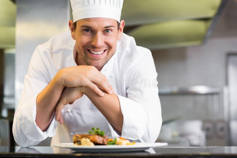 微笑的男性厨师用熟食在厨房里 免版税库存图片