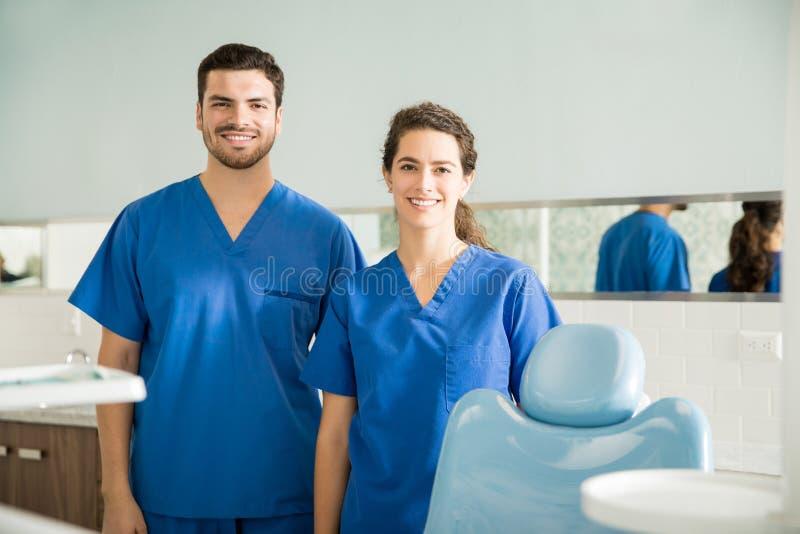 微笑的男性和女性牙医画象诊所的 库存图片