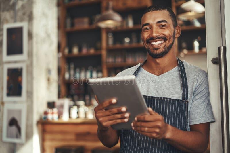 微笑的男性咖啡馆所有者在他的手上的拿着数字片剂 免版税库存照片