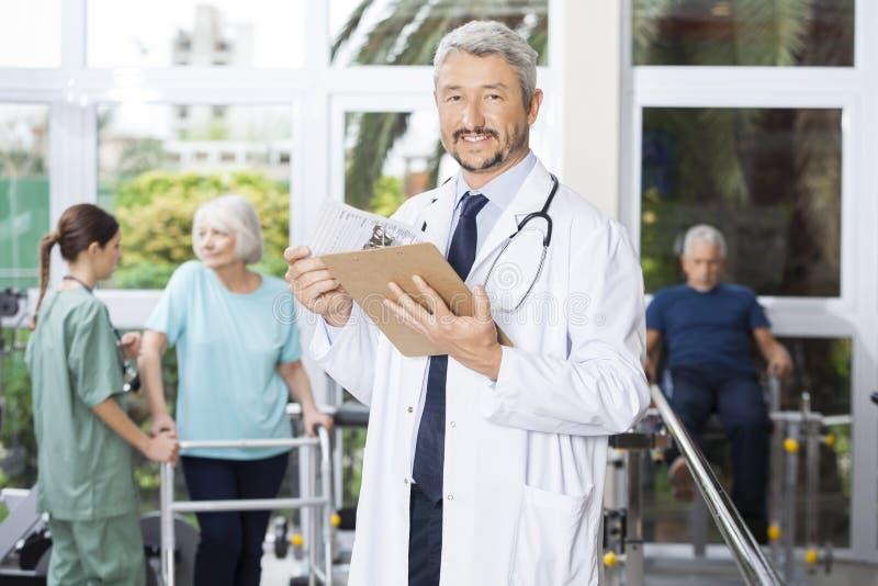 微笑的男性生理治疗师在健身中心的拿着剪贴板 免版税库存照片