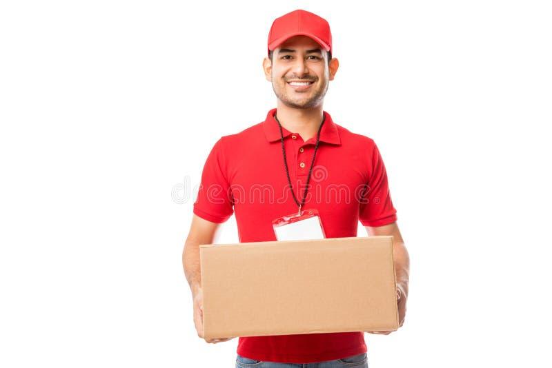 微笑的男性运载的交付包裹画象  免版税图库摄影