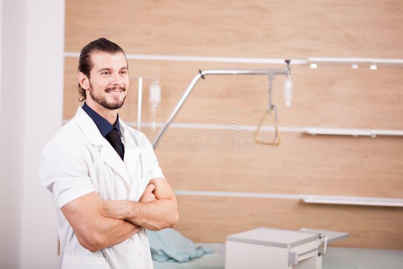 微笑的男性医生画象医院背景的 免版税图库摄影