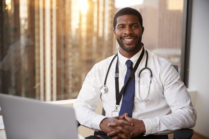 微笑的男性With Stethoscope In Hospital医生办公室画象  库存图片