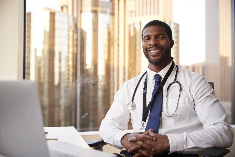微笑的男性With Stethoscope In Hospital医生办公室画象  免版税库存图片