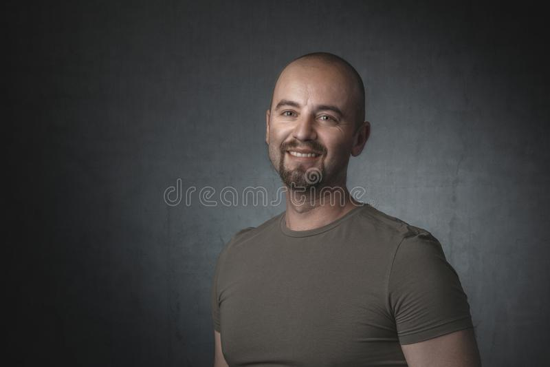 微笑的白种人人画象有T恤杉和黑暗的背景的 库存照片