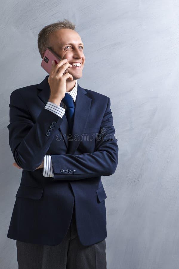 微笑的白种人人Portarit蓝色衣服的发表演讲关于手机 摆在对难看的东西墙壁 库存图片