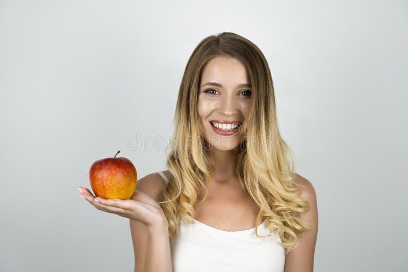 微笑的白肤金发的可爱的妇女在一手被隔绝的白色背景中的拿着水多的红色苹果 库存图片