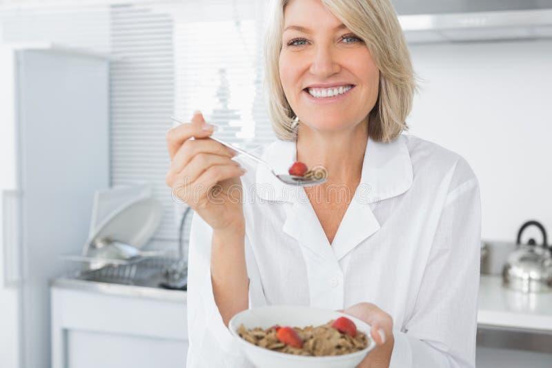 微笑的白肤金发的吃谷物早餐 库存图片