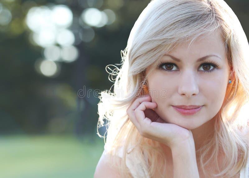 微笑的白肤金发的女孩。愉快的美丽的少妇画象,户外。Bokeh 图库摄影