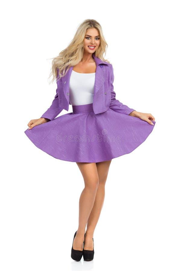 微笑的白肤金发的妇女在紫罗兰色微型裙子、夹克和高跟鞋摆在 免版税库存图片