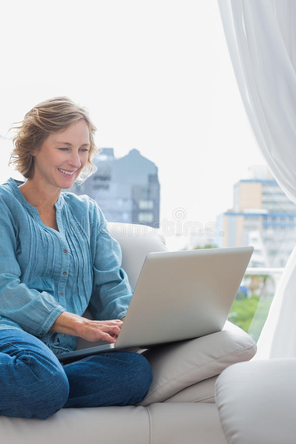 微笑的白肤金发的妇女坐她的长沙发使用膝上型计算机 免版税库存照片