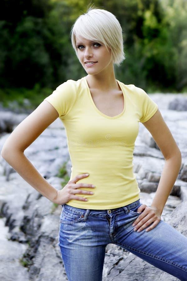 微笑的白肤金发的妇女户外画象 库存图片