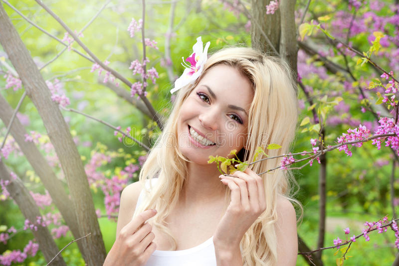 微笑的白肤金发的妇女秀丽画象,完善新鲜的皮肤和健康白色微笑,每日基本的构成,有兰花花的长的头发 库存照片