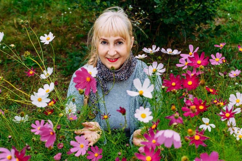 微笑的白肤金发的妇女退休的和开花的翠菊在庭院里在夏天 图库摄影