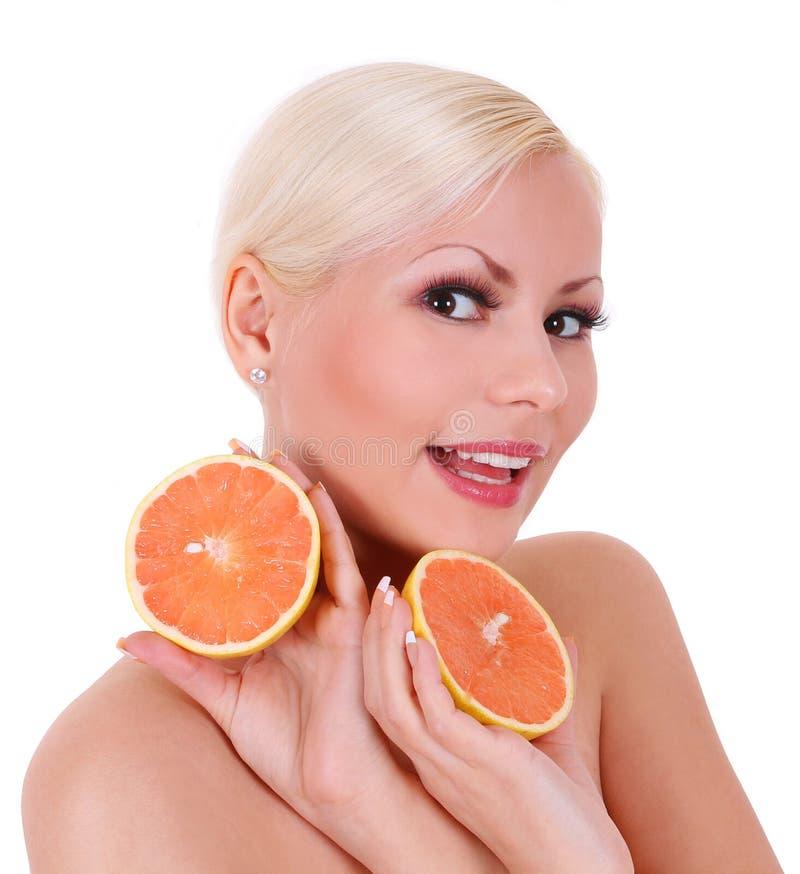 微笑的白肤金发的少妇用查出的橙色果子 免版税库存图片