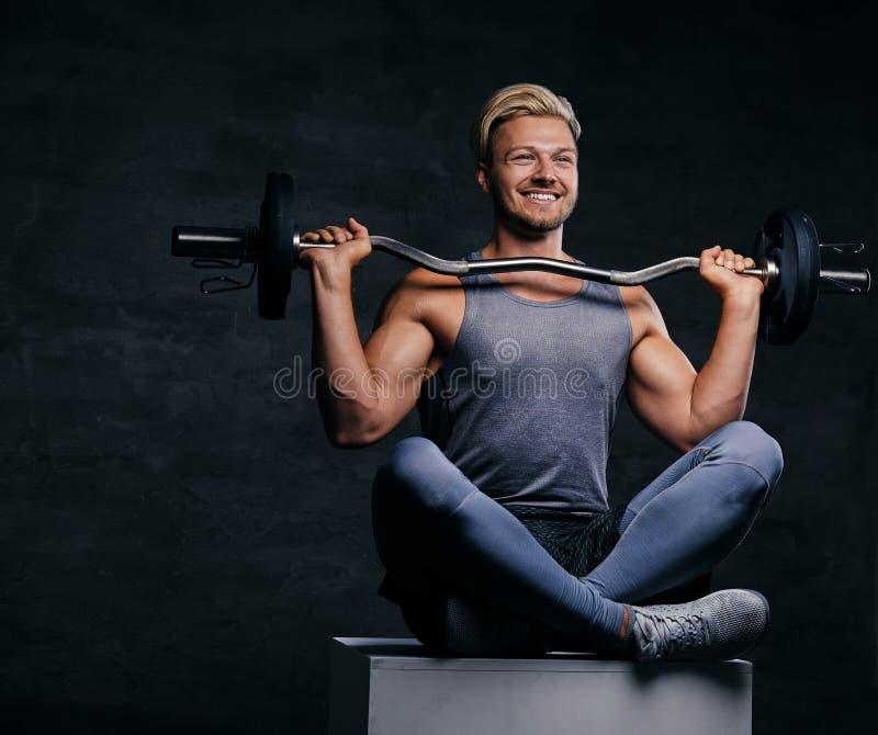 微笑的白肤金发的运动的男性坐有盘的腿的白色箱子并且拿着杠铃 免版税库存照片
