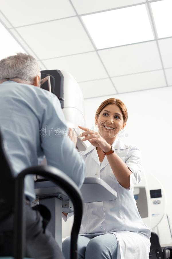 微笑的眼科医生,当监测人时眼睛视域  免版税库存照片