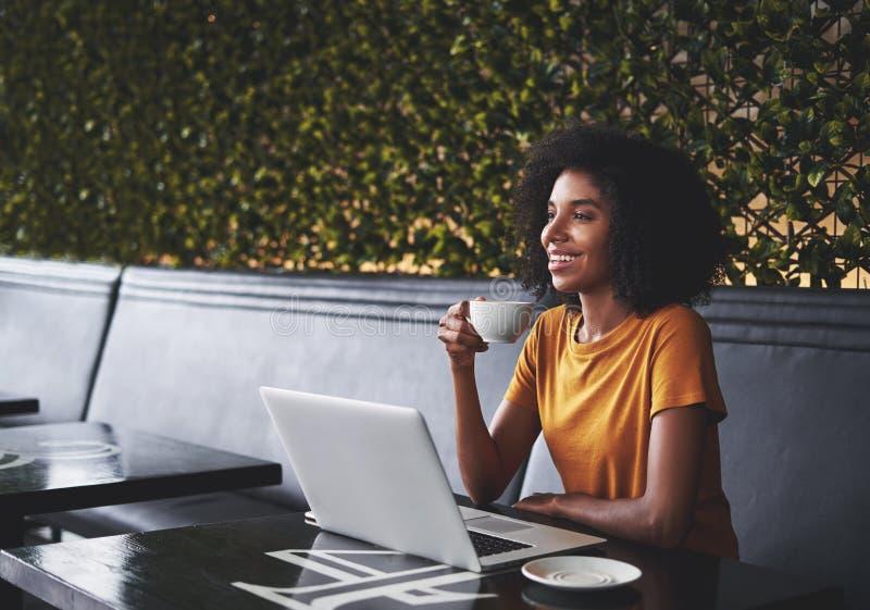 微笑的确信的年轻女人在与膝上型计算机的咖啡馆坐桌 免版税图库摄影