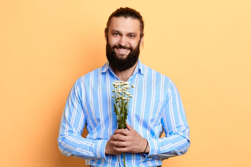微笑的种类有胡子的时髦的人在他的手上的拿着花 库存图片