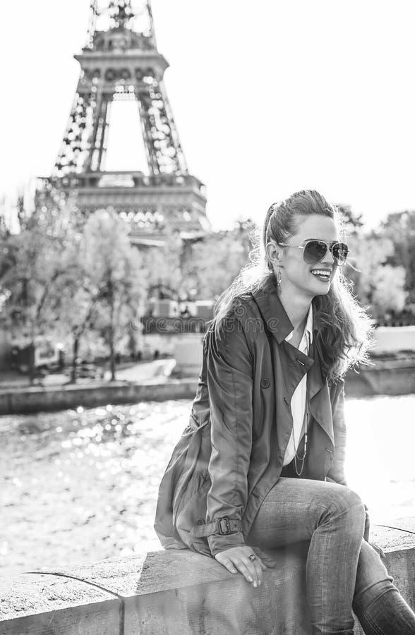 微笑的端庄的妇女坐栏杆在巴黎,法国 图库摄影