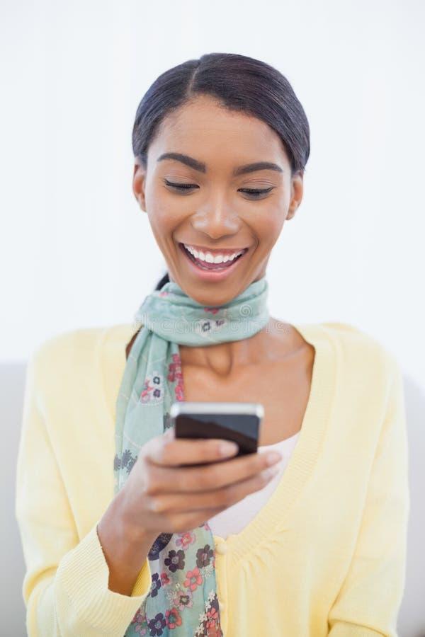 微笑的端庄的妇女坐沙发正文消息 库存图片