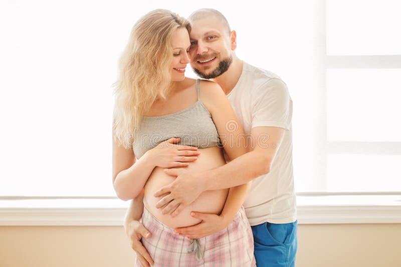 微笑的笑的白色白种人年轻中年夫妇,有丈夫的孕妇画象在拥抱拥抱的屋子里 免版税库存照片