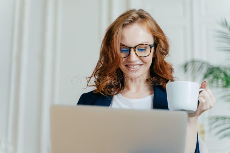 微笑的红发女性特写光学玻璃的,享用热的咖啡或茶,聚焦在手提电脑,做购买 免版税库存图片