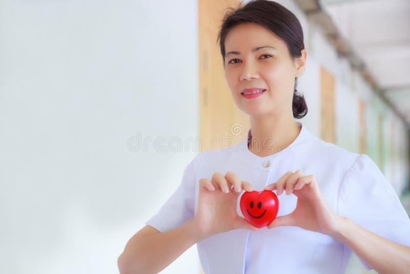 微笑的红色心脏由在医疗保健医院或诊所的微笑的女性护士` s手举行了 专家,专家,被体验 免版税图库摄影