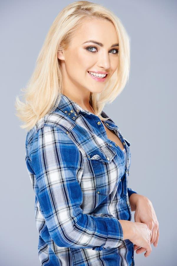 微笑的美丽白肤金发在一件被检查的蓝色衬衣 免版税库存照片