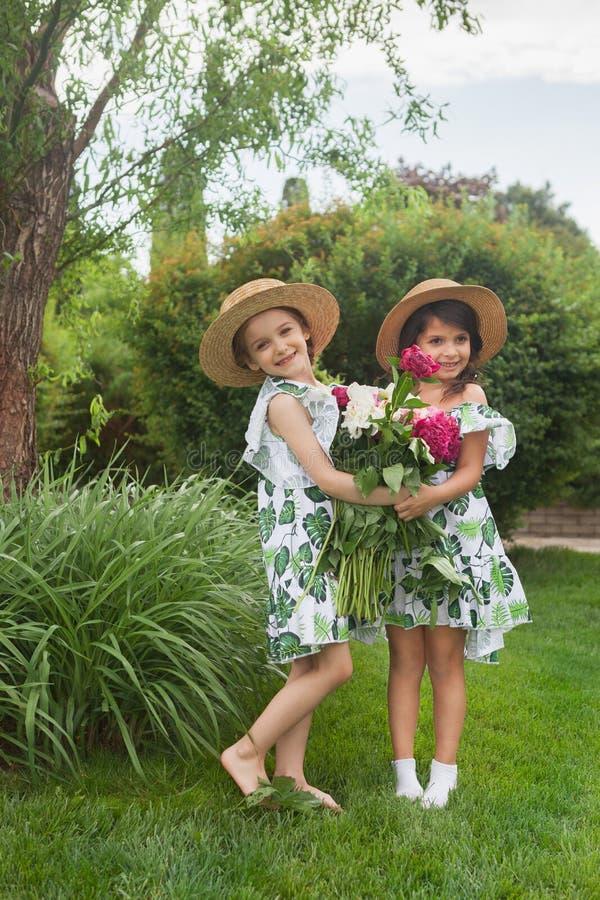 微笑的美丽的女孩画象有牡丹花束的反对绿草的在夏天公园 免版税库存照片