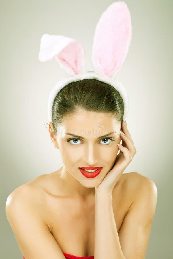 微笑的美丽的妇女佩带的兔宝宝耳朵 库存照片