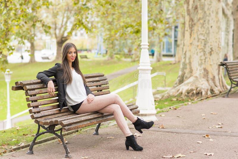 微笑的美丽的妇女坐木长凳,室外 库存图片