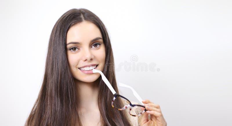 微笑的美丽的妇女画象有眼镜在手中isol的 免版税库存照片