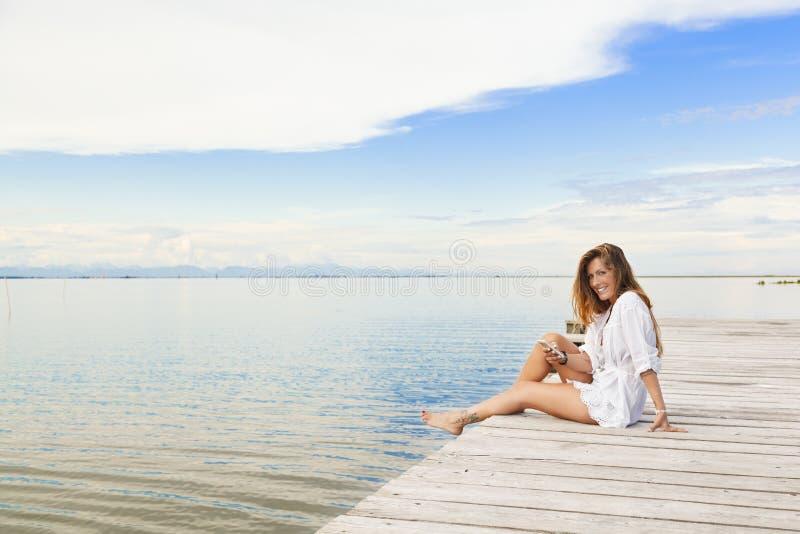 微笑的美丽的少妇坐码头和使用mobi 免版税库存照片
