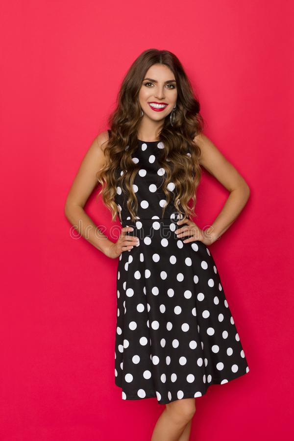 微笑的美丽的年轻女人在圆点的黑Coctail礼服摆在 图库摄影