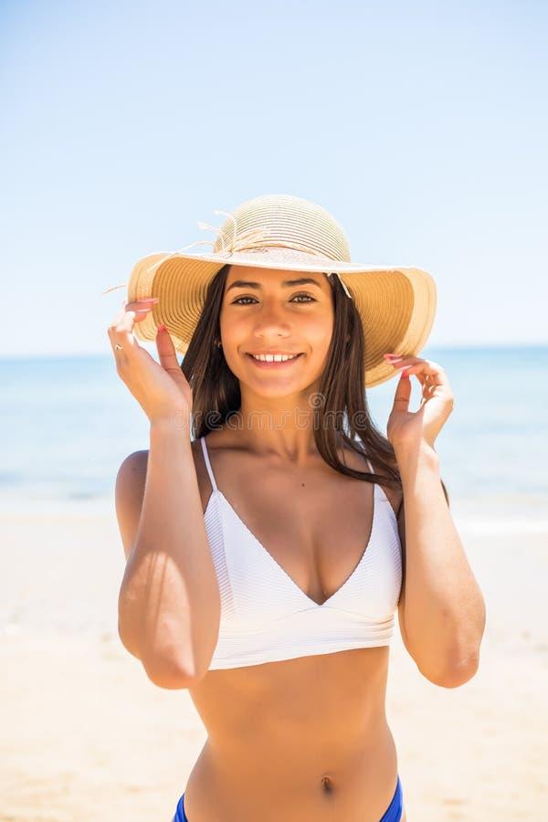 微笑的美丽的年轻女人特写镜头海滩的与在海海滩的草帽 库存照片